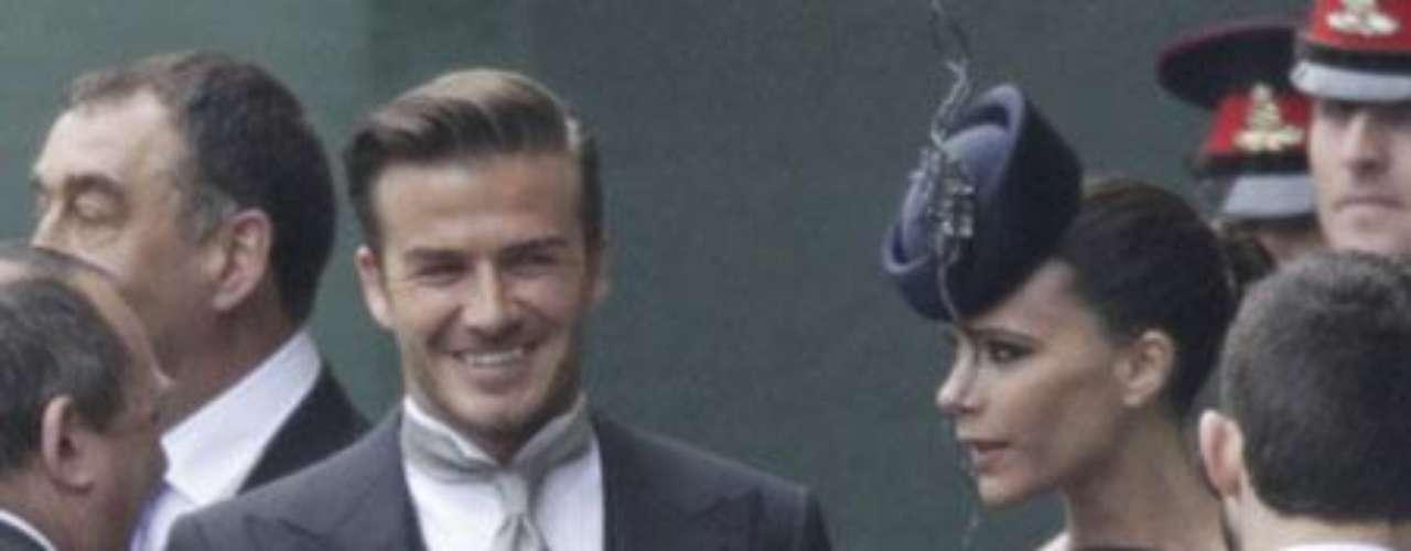David Beckham, con la cruz de la Orden del Imperio británico que le impuso su majestad la Reina Isabel II  y su mujer Victoria.