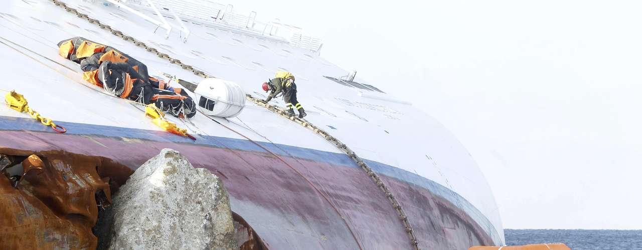 Bomberos italianos se disponen a reanudar los preparativos para vaciar de combustible el crucero encallado Costa Concordia en la isla toscana de Giglio el domingo 5 de febrero del 2012. El Concordia encalló el 13 de enero con 2.000 toneladas (500.000 galones) de diesel.