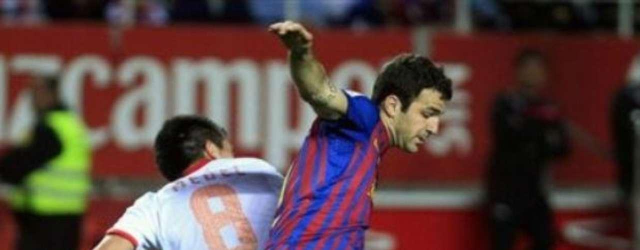 Gary Medel del Sevilla y Cesc Fabregas del Barecelona disputan el esférico en el centro del campo.