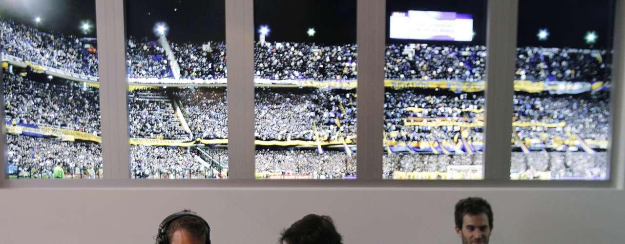 Periodistas dialogan junto a una imagen en movimiento de la afición del club Boca Juniors en el Hotel Boca Juniors.