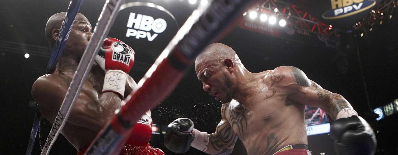 Miguel Cotto ataca a Floyd Mayweather Jr. y lo pone contra las cuerdas en su pelea.  (AP Photo/Eric Jamison)