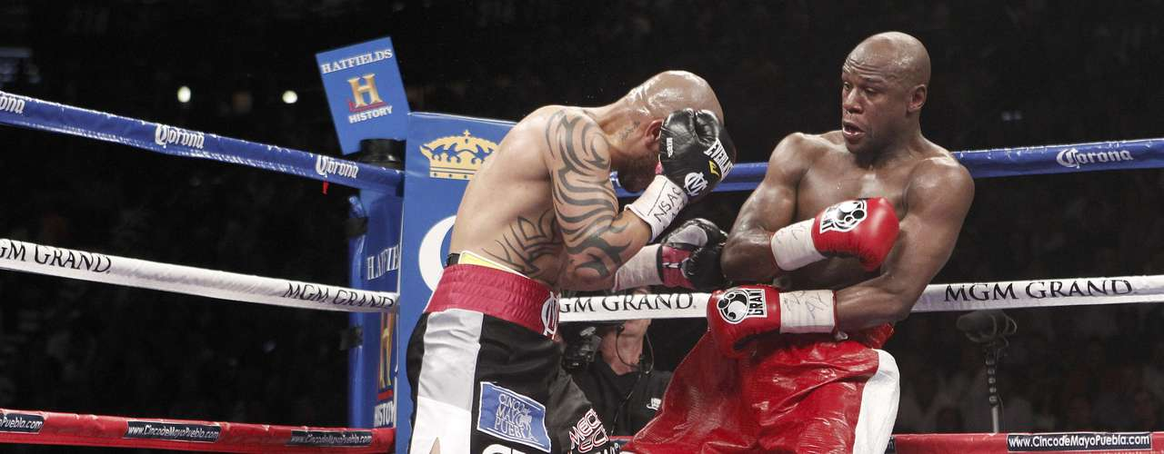 Miguel Cotto lanza un golpe perfecto ante Floyd Mayweather Jr. y lo pone contra las cuerdas en su pelea.  (AP Photo/Eric Jamison)