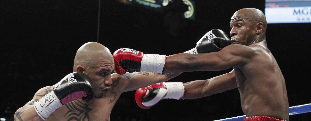 Miguel Cotto golpea a Floyd Mayweather Jr. en su pelea por el título superwelter.  (AP Photo/Eric Jamison)