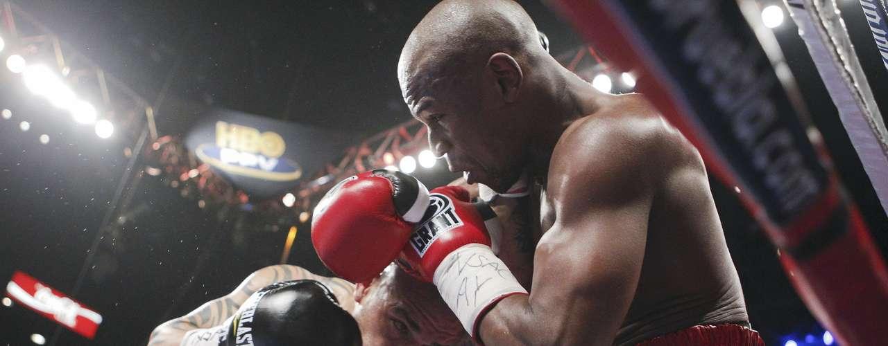 Miguel Cotto y Floyd Mayweather Jr. intercambian golpes en su pelea en Las Vegas.  (AP Photo/Eric Jamison)