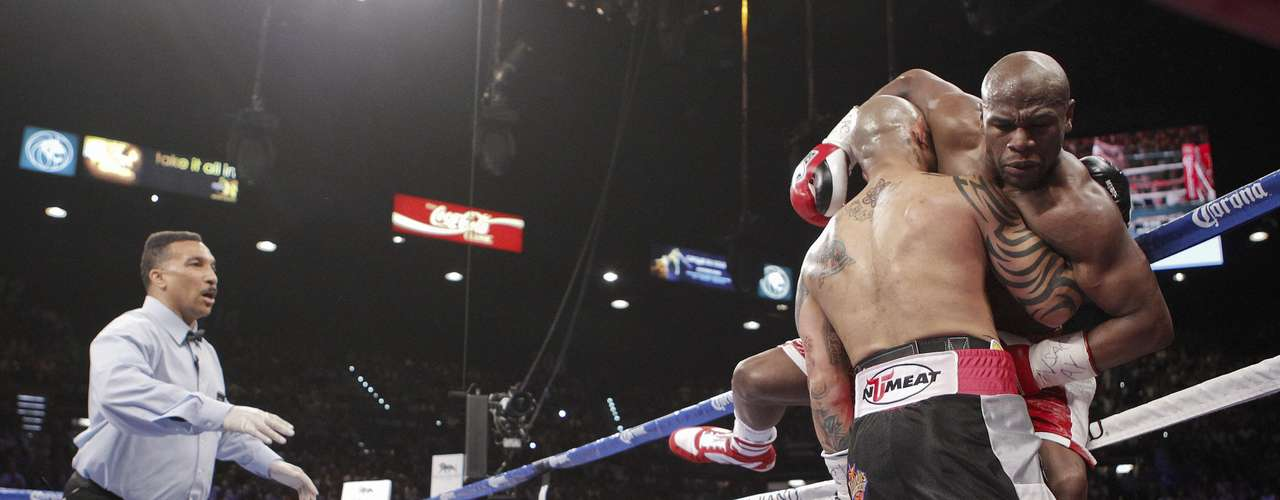 Miguel Cotto carga Floyd Mayweather Jr. ante la complacencia del referí Tony Weeks.  (AP Photo/Eric Jamison)