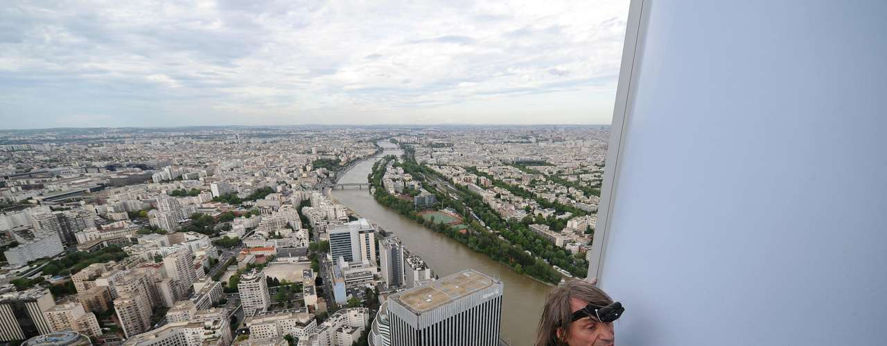 Alain Robert escaló el jueves la recientemente construida torre First en el distrito comercial de La Defense al oeste de la capital. Cientos de personas se detuvieron a ver la hazaña, estirando los cuellos mientras Robert subía y subía.