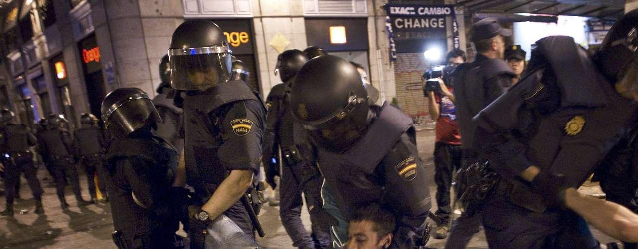 Policías retirando a manifestantes que se negaban a desalojar la Puerta del Sol en la madrugada de este domingo, cuando los últimos 'indignados' que quedaban fueron obligados a marcharse.