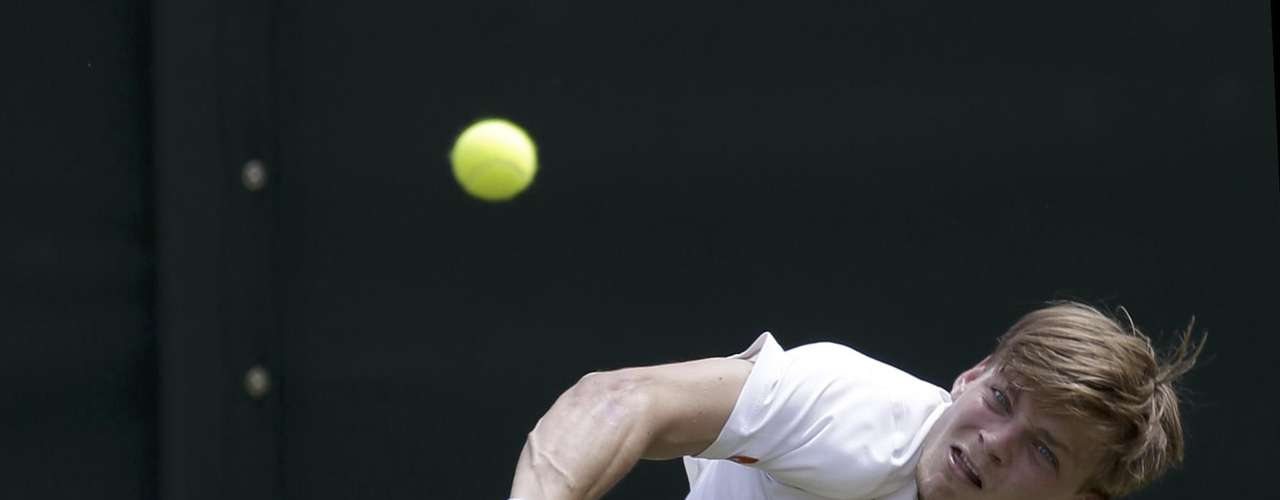 David Goffin of Belgium serves to Bernard Tomic of Australia during a first round men's singles match at the All England Lawn Tennis Championships at Wimbledon, England, Tuesday, June 26, 2012. (AP Photo/Alastair Grant)