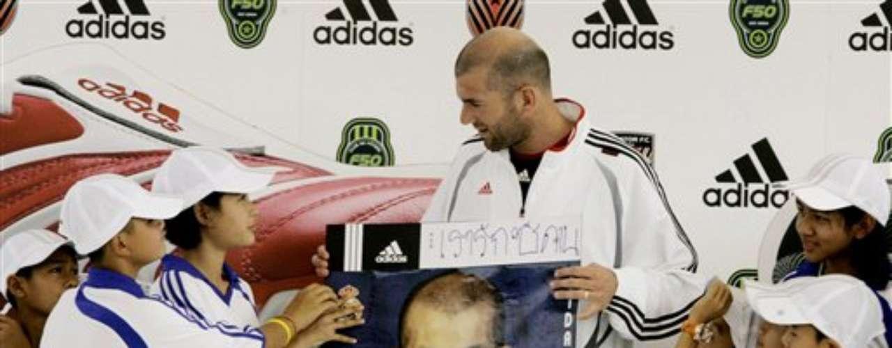 El ex futbolista francés, Zinedine Zidane, a pesar de dejar las canchas, no dejó de lado su buen corazón. Hace partidos benéficos y en esta imagen tomada en 2007, recibe una foto que dice en inglés \