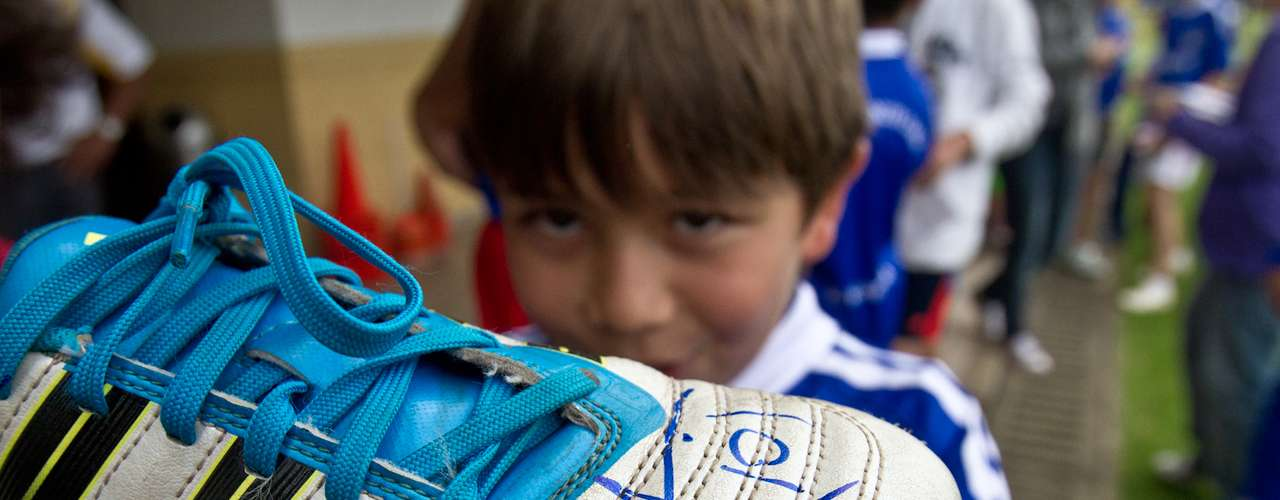 Niño de una filial de la Escuela de Formación de Independiente Santa Fe muestran los autógrafos que le firmaron los jugadores.