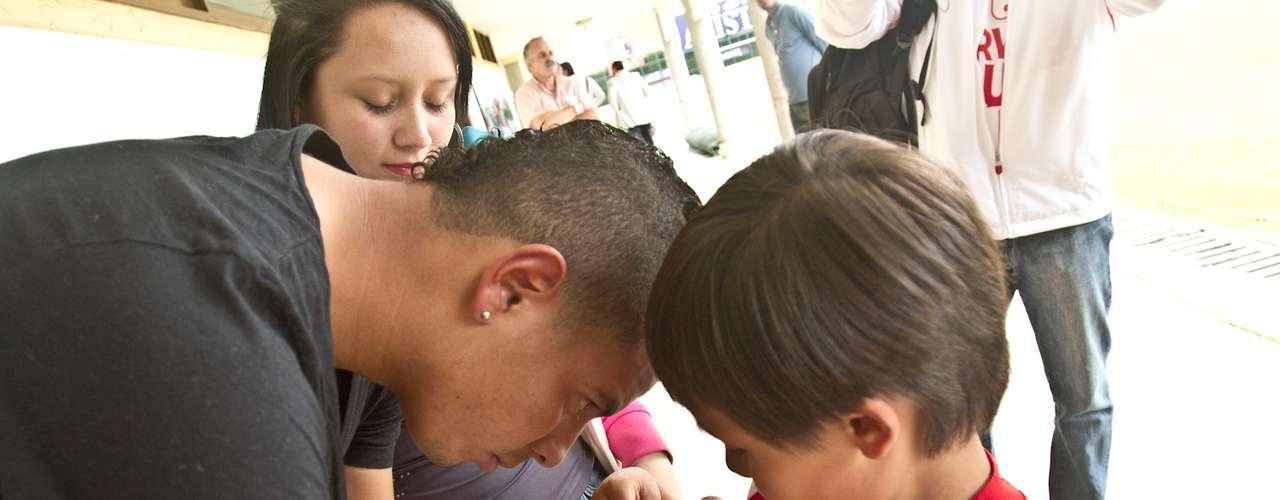 Edwin Cardona, volante de Independiente Santa Fe firma autógrafos y se toma fotos con niños de una filial de la Escuela de Formación del rojo.