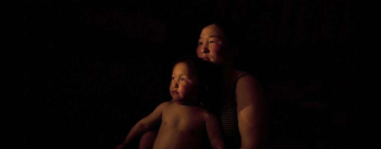 En esta foto Erdene posa junto a su hijo de tres años, Tuvchinj, una noche justo antes de acostarse. Las personas retratadas comparten un destino común: son pastoras y pastores que se vieron obligados a abandonar las zonas rurales y aisladas donde vivían y dirigirse a la ciudad.