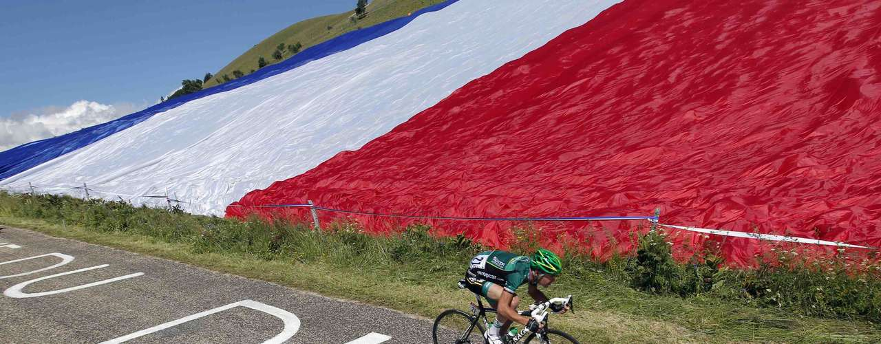Team Europcar rider Thomas Voeckler of France cycles past a giant French flag during the tenth stage of the 99th Tour de France cycling race between Macon and Bellegarde-sur-Valserine, July 11, 2012.