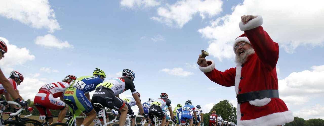 The pack of riders cycle past a spectator dressed as Santa Claus during the tenth stage of the 99th Tour de France cycling race between Macon and Bellegarde-sur-Valserine, July 11, 2012.