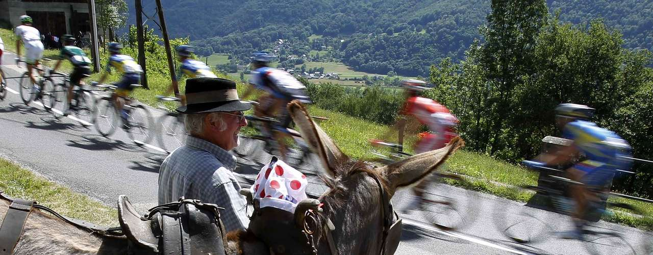 The pack of riders cycles past a spectator with a donkey during the 12th stage.