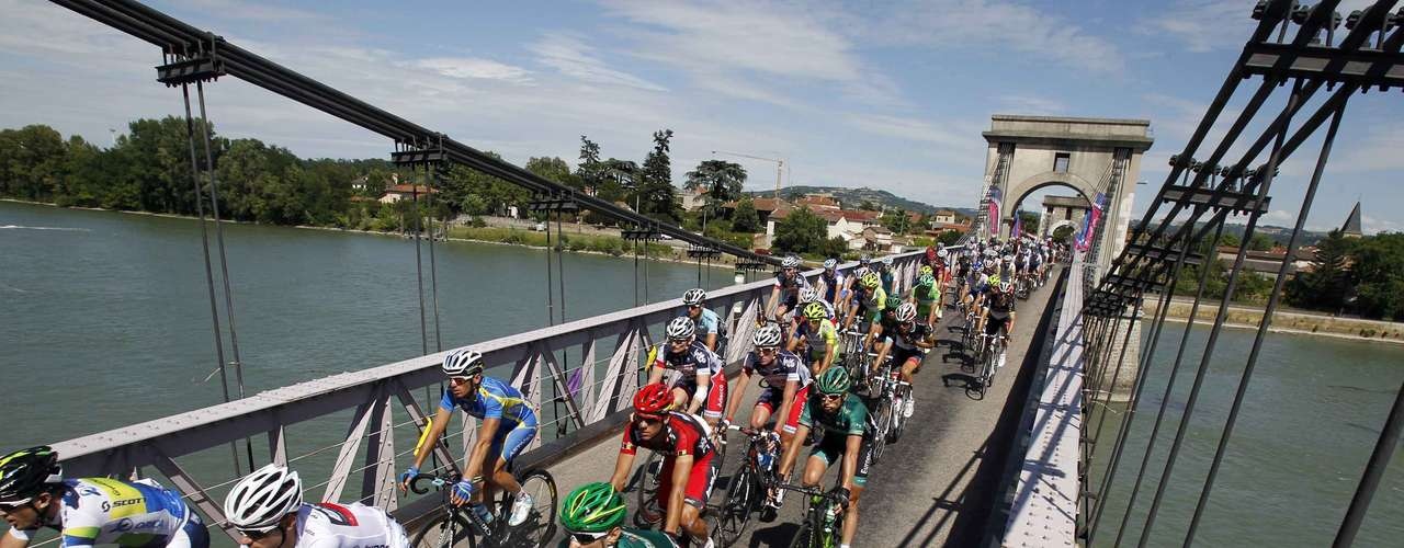 The pack of riders cycles on a bridge during the 12th stage of the 99th Tour de France cycling race between Saint-Jean-de-Maurienne and Annonay-Davezieux, July 13, 2012.