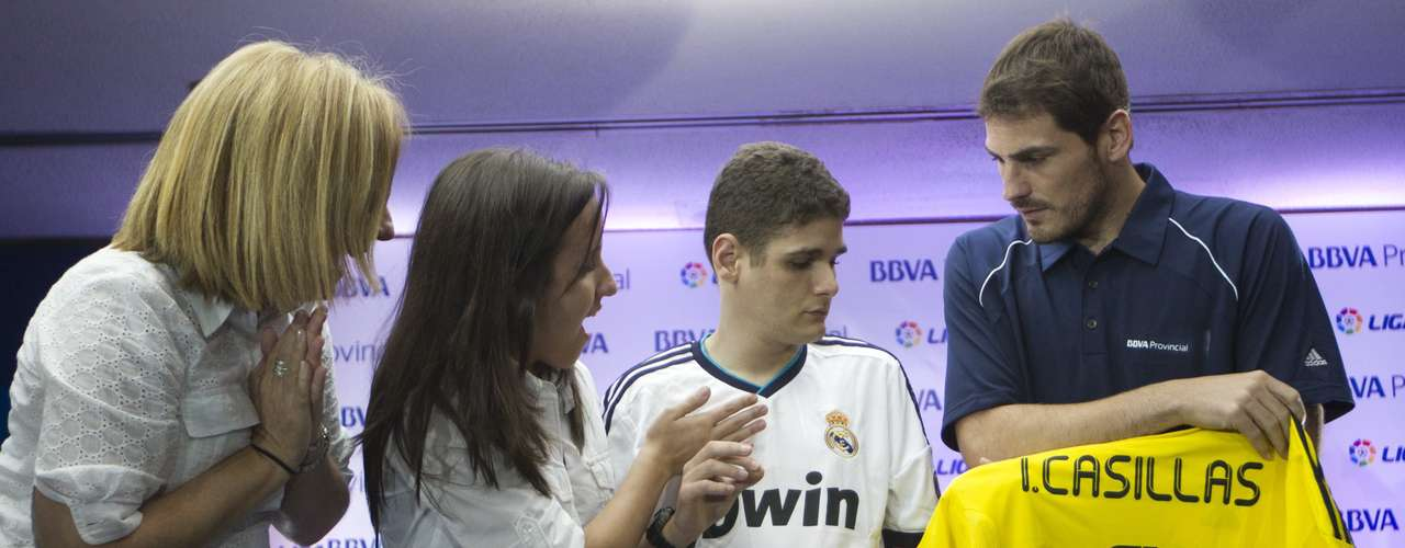 Spain's national soccer team captain Iker Casillas (R) gives a signed jersey to a young fan with special needs after a news conference in Caracas July 16, 2012. Casillas was in Venezuela to attend a coaching clinic for children in Caracas. REUTERS/Carlos Garcia Rawlins (VENEZUELA - Tags: SPORT SOCCER)