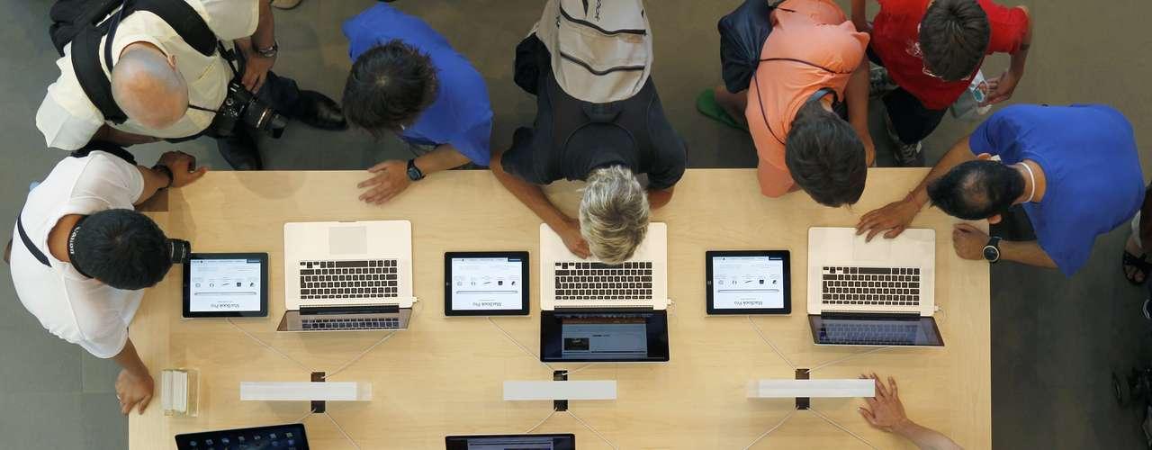 Empleados y clientes rodean una mesa con MacBook Pro, durante la inauguración oficial de la tienda más grande de Apple.