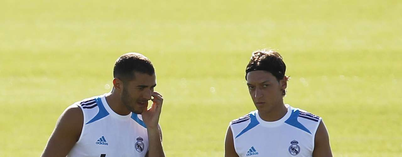Karim Benzema (L) talks to team mate Mesut Ozil during a training session at Real Madrid's training grounds in Valdebebas, outside Madrid, August 16, 2012.    REUTERS/Susana Vera (SPAIN - Tags: SPORT SOCCER)