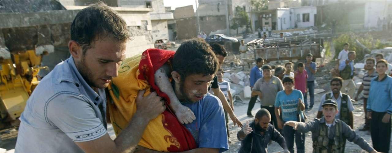 Dos hombres transportan el cuerpo de un niño extraído de los escombros de su casa.