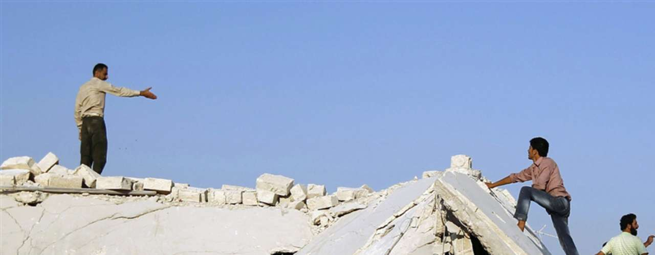 Dos hombres discuten la mejor manera de retirar los escombros de un edificio derrumbado tras el bombardeo de Asaz.