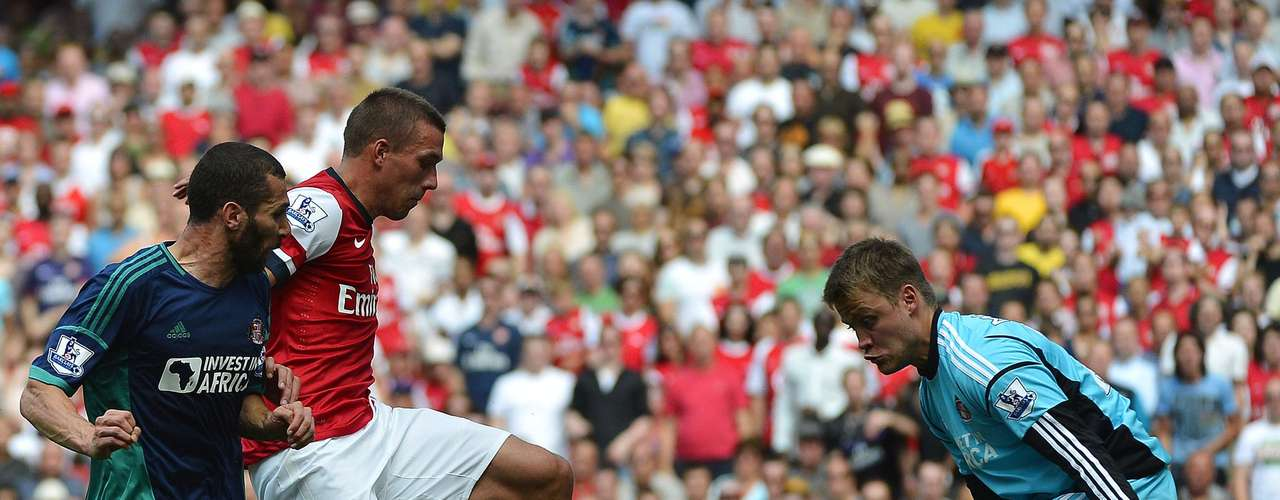 Arsenal's Lukas Podolski (C) shoots as Sunderland's goalkeeper Simon Mignolet (R) looks on during their English Premier League soccer match.