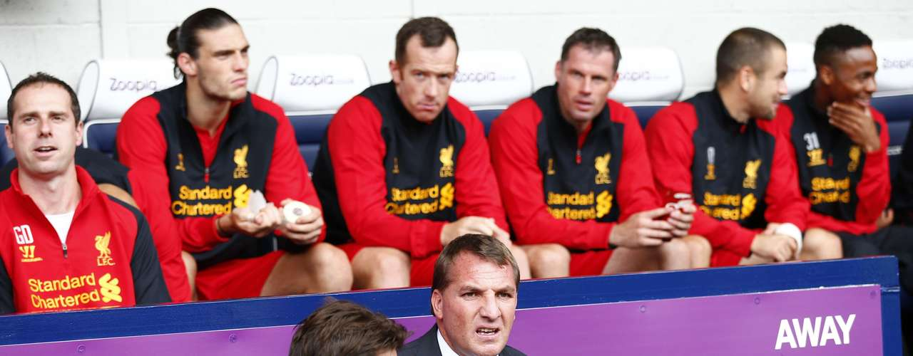 Liverpool's Manager Brendan Rodgers (front R) sits on the bench after losing in its debut.