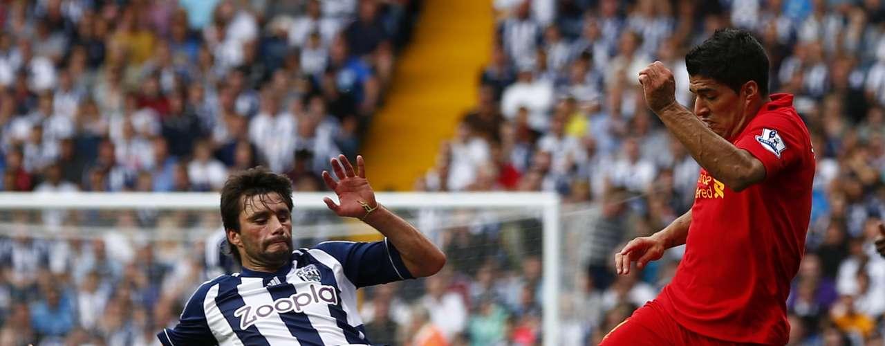 West Bromwich Albion's Claudio Yacob (L) challenges Liverpool's Luis Suarez.