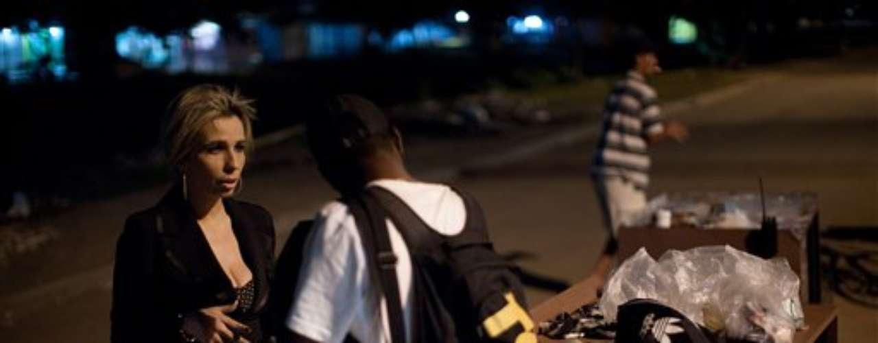 Cuando camina por las favelas con tacos de 15 centímetros (seis pulgadas) y jeans con imitaciones de piedras preciosas, recorriendo calles llenas de pozos, individuos con armas en las dos manos se muestran respetuosos y le dicen \