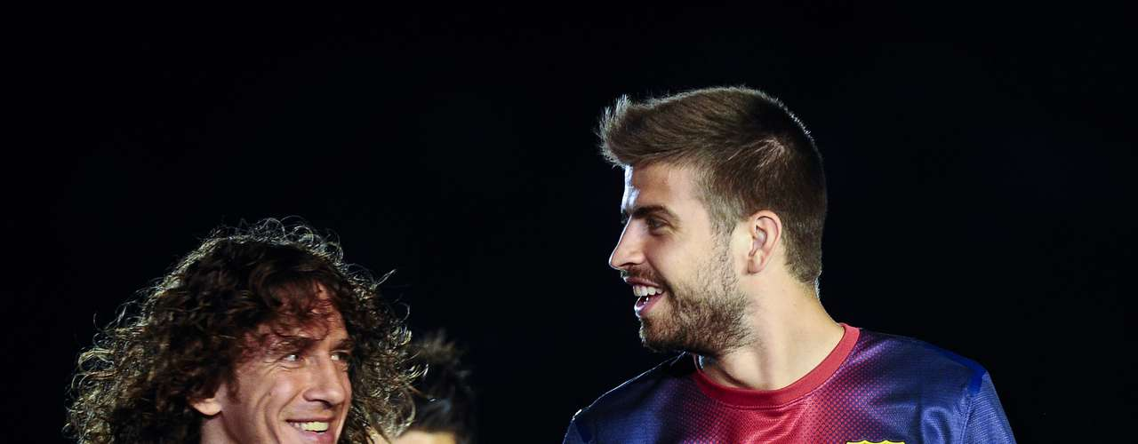 Carles Puyol and Gerard Pique walk to the center of the field before the team's presentation