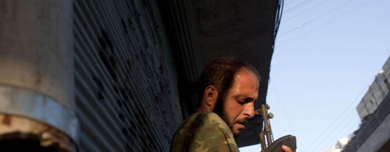 Un rebelde recarga su rifle Kalasnikhov mientras se resguarda de un helicóptero de la fuerza aérea siria durante los combates del martes, 21 de agosto