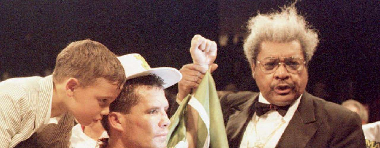 Julio Cesar Chavez (C) of Mexico is surrounded by his son Julio Jr (L) and promoter Don King (R) after judges awarded Chavez a victory in his WBC Super Lightweight Championship bout with Frankie Randall. Chavez won the 07 May 1994 bout after an injury from a head butt from Randall stopped the fight in the eighth round.