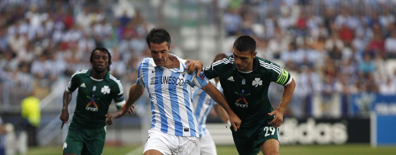 Malaga's Jeremy Toulalan (2nd L) fights for the ball with Panathinaikos' Kostas Katsouranis. REUTERS/Jon Nazca