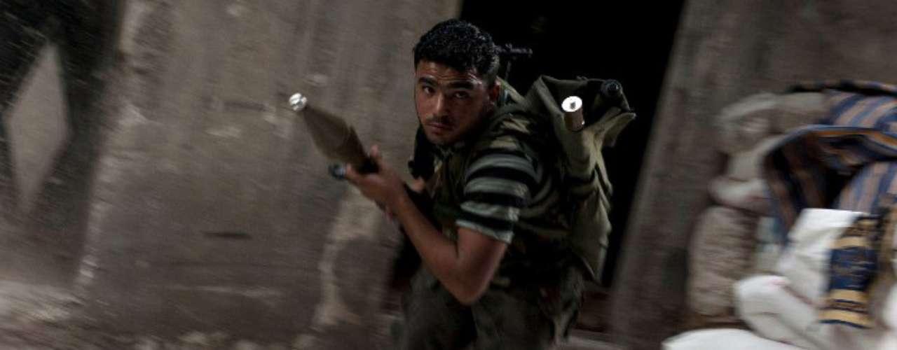 Un integrante del Ejército Sirio de Liberación, el principal grupo armado rebelde, se agacha para evitar los tiros de las fuerzas leales a Bashar Al Asad.