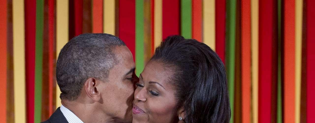 No hacen falta paparazzis para captarlos muy cariñosos, pues los políticos de EE.UU. se demuestran el amor ante los ojos del público. Quizás, una manera de identificarse con los votantes o simplemente pura espontaneidad, pero el caso es que son muy pocos los que se escapan del lente fotográfico. En esta foto del 20 de agosto de 2012 el presidente Barack Obama besa a la Primera Dama, Michelle, antes de hablar en una cena de Estado para niños como parte de la campaña \