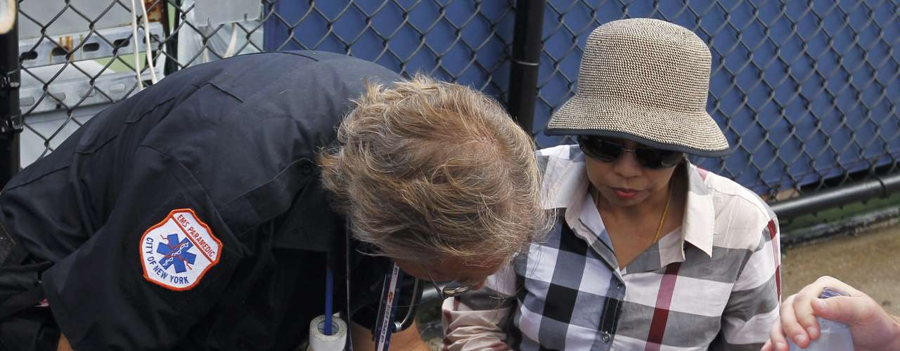 A ball girl is attended to after collapsing in the heat at the U.S. Open tennis tournament in New York, August 28, 2012. REUTERS/Lucas Jackson (UNITED STATES  - Tags: SPORT TENNIS ENVIRONMENT)