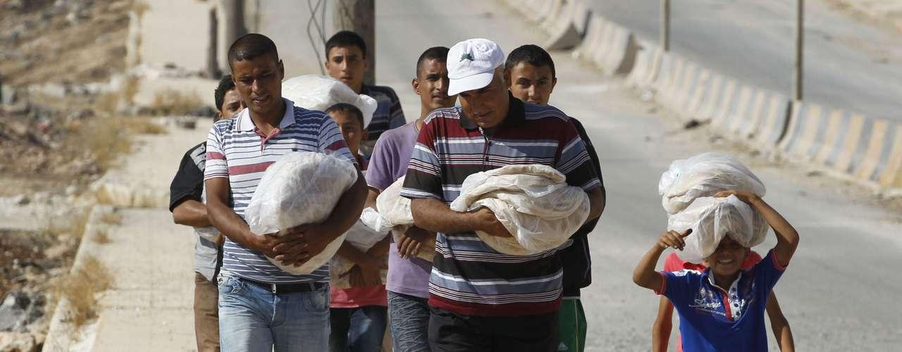 Refugiados portando sus raciones de pan en Bab Al-Salam, principal campamento en suelo truco.