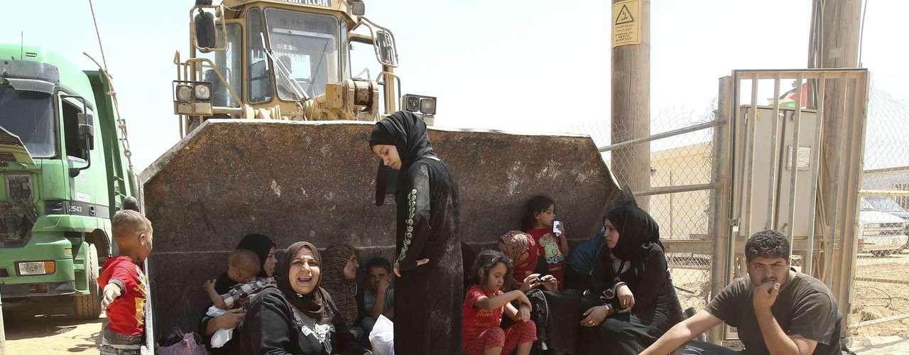 Un grupo de refugiados sirios descansa a la espera de que se les asigne una tienda en el campamento de Al Za'atri, tras recorrer la distancia que lo separa de la frontera con Siria (86 kilómetros).