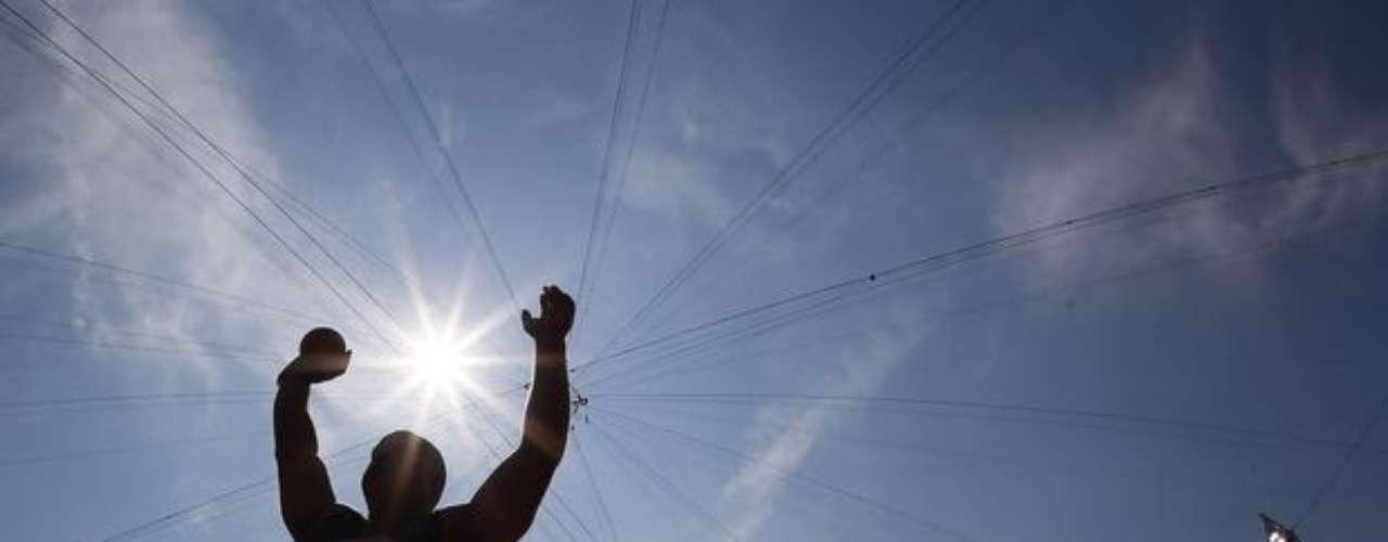 Bajo un sol hirviente, el australiano Russel Short se prepara para el lanzamiento de peso.