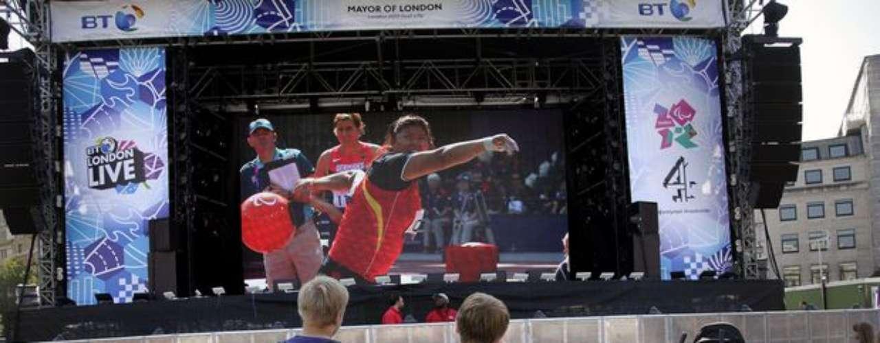 En una pantalla gigante, instalada en la Trafalgar Square, en el centro de Londres, personas en sillas de ruedas siguen la prueba de lanzamiento de peso en los Juegos Paralímpicos.