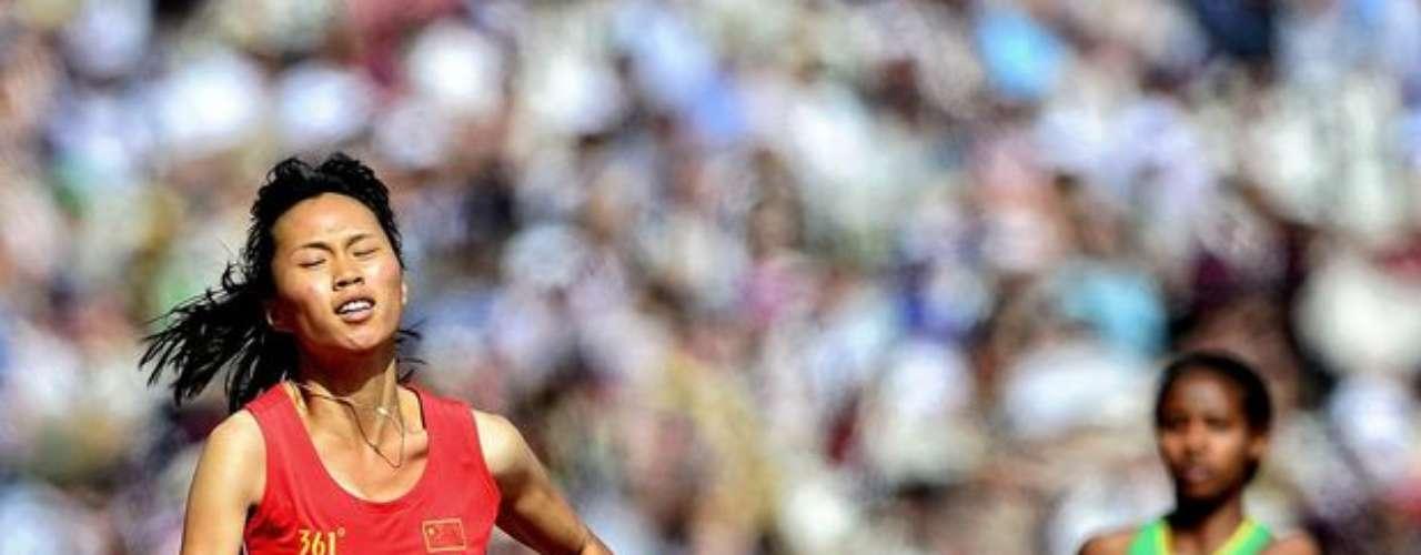 Una atleta china sufre con el calor londinense durante la realización de las pruebas de atletismo.