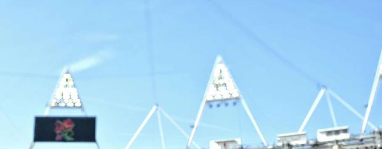 Un atleta disputa prueba de salto con el Estadio Olímpico totalmente lleno.