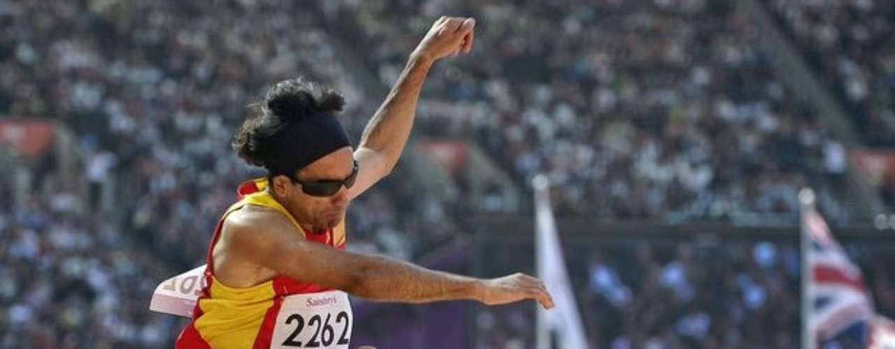 Árbitros observan la ejecución del salto de un atleta.