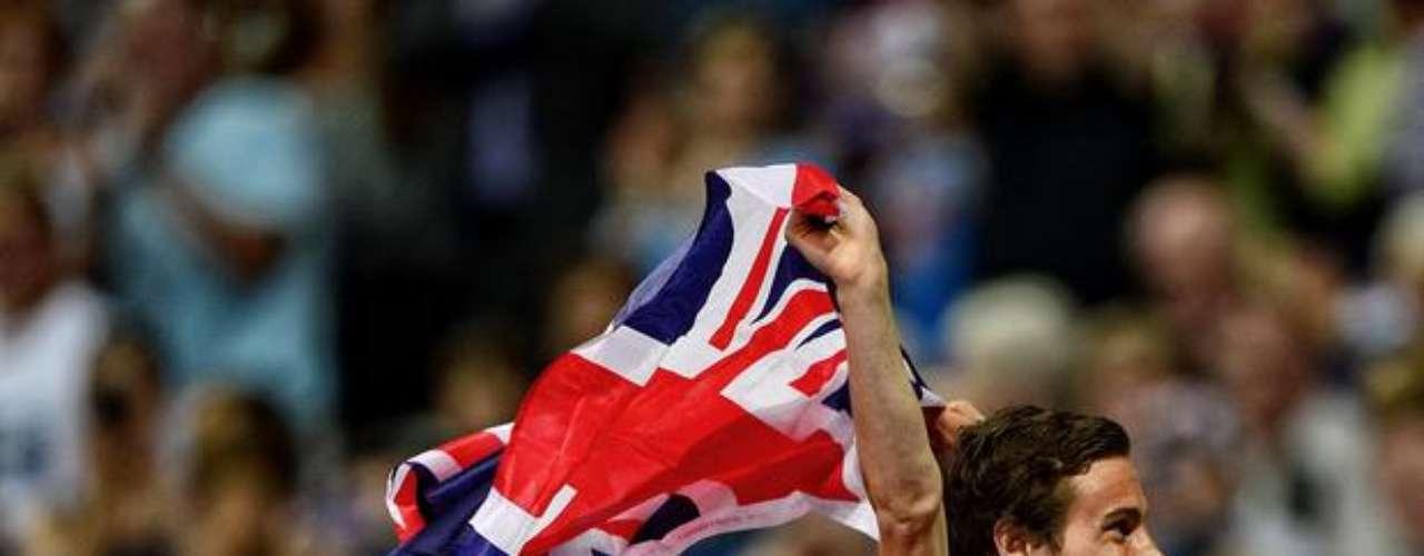 Medallista de plata en los 400 m, Paul Blake festeja el resultado de la carrera con la bandera británica.