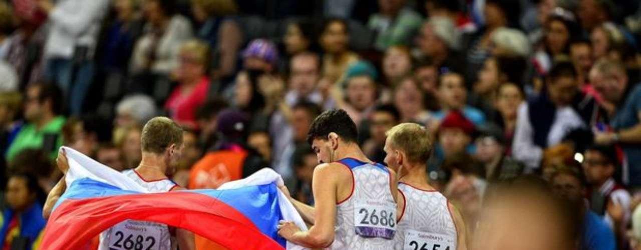 Tres deportistas rusos sostienen la bandera de su país para festejar el final de una carrera.
