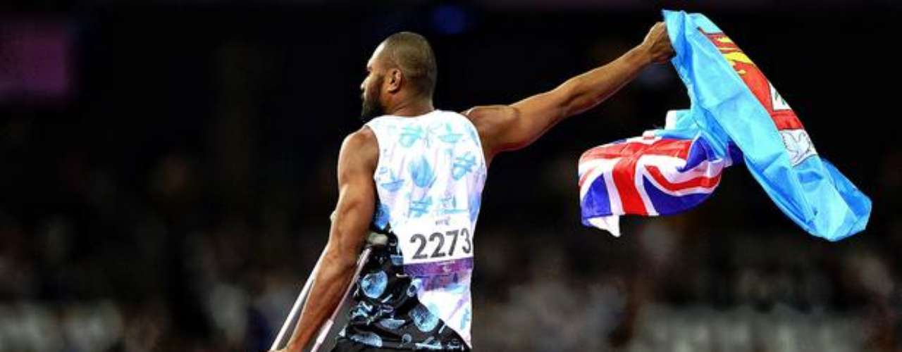 Este atleta agita la bandera de Fiyi sobre la colchoneta de la prueba de salto de altura.