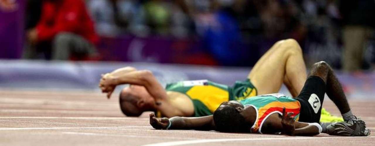 Estos atletas se acuestan en la pista para descansar después de la prueba.