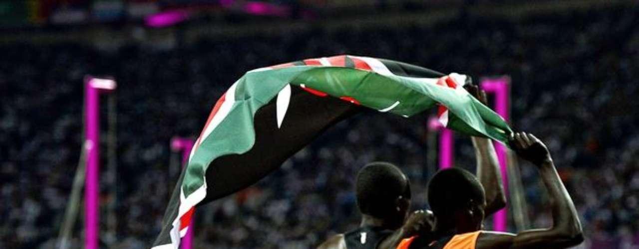 Un atleta keniano y su guía agitan la bandera de su país tras el final de la carrera.