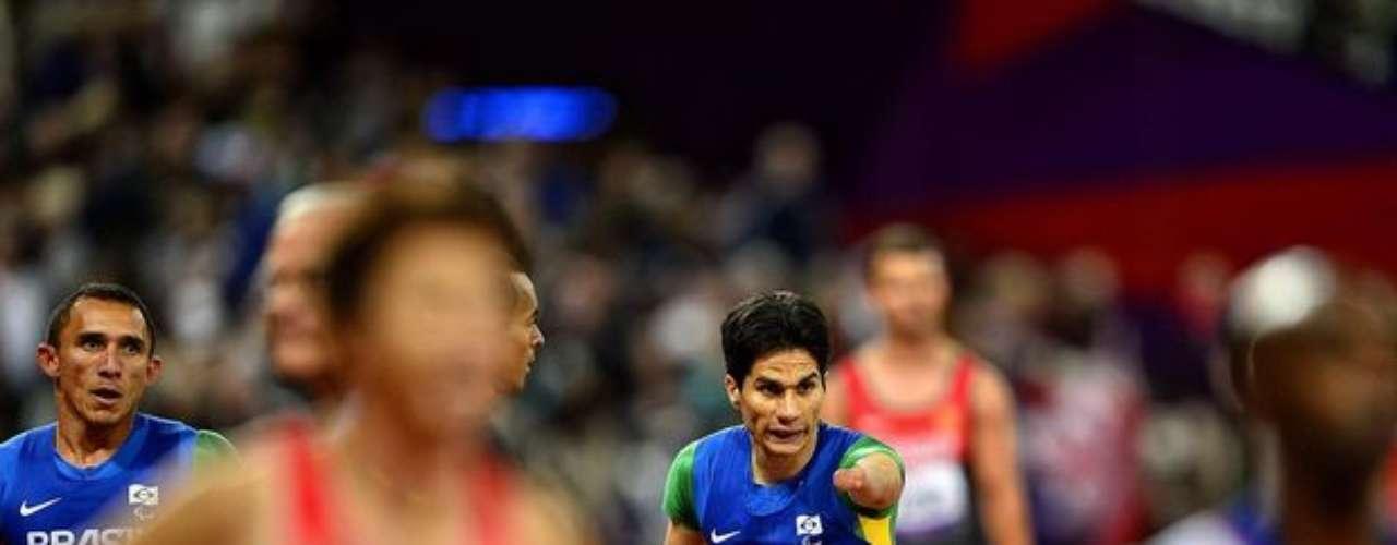 Los atletas esperan el resultado oficial del relevo 4x100 m, en el Estadio Olímpico.
