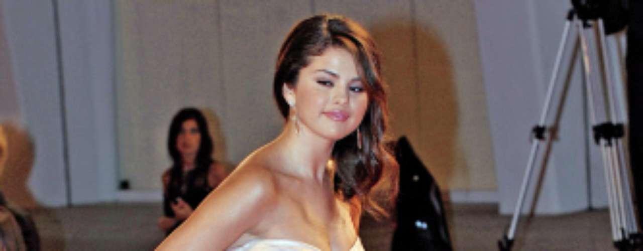 La actriz Selena Gomez apareció en la alfombra roja del festival de Cine con un glamouroso y sofisticado vestido con escote palabra de honor y sandalias con plataforma a juego con el vestido.